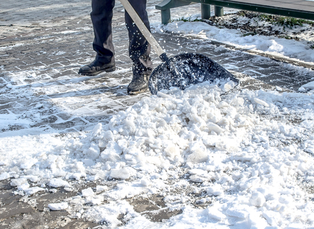 Cleaning the snow in a hand shovel in the park