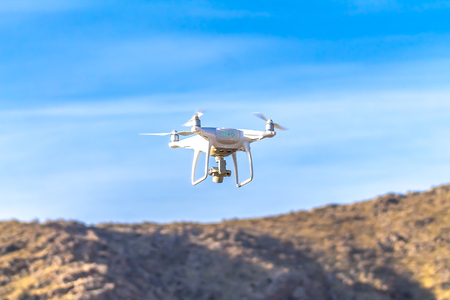 drone quad copter with high resolution digital camera flying hovering in the blue sky.