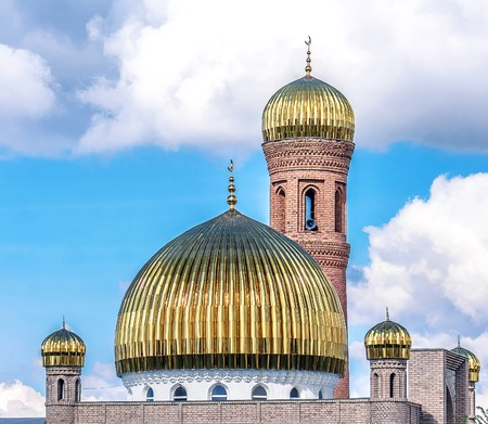 The Muslim mosque of the golden dome on the background of the sky with clouds