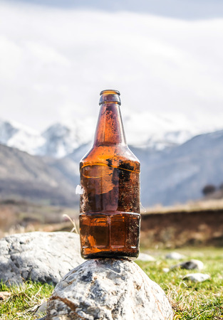 Old plastic bottles on the background of the mountains pollution