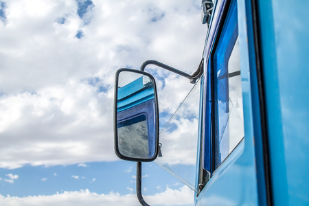 Side mirror of a lorry with clouds and blue sky background.