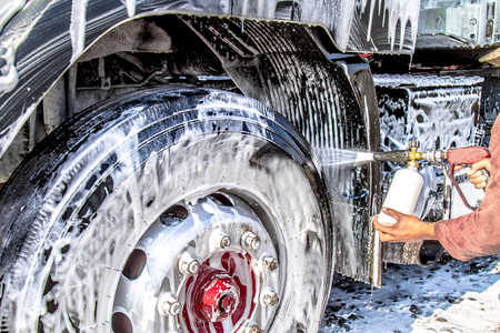 A worker washing a big truck close-up