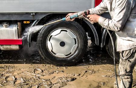 A man washing big truck with a hose