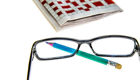 Glasses, newspaper with crossword and pencil on the table Stock Photo