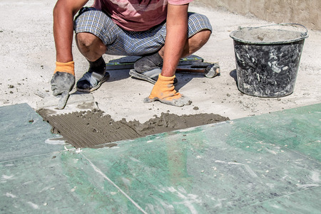 A worker laying tiles from porcelain stoneware Фото со стока - 109687529