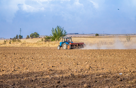 Tractor with a seeder on a field
