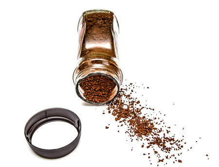 Instant coffee scattered from a can on a white background