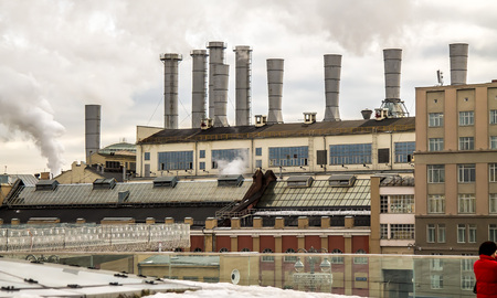 The building of the boiler room with smoking chimneys in the city