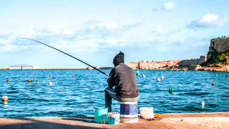 Fisherman with a fishing rod on the seashore landscape