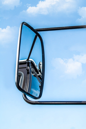 Car mirror against the sky