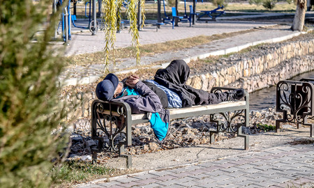 Alcoholic homeless man sleeping on a park bench