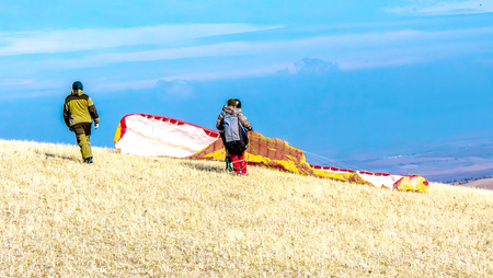 Paraglider prepares to fly in the open air.Parachute in the backpack outdoors Stock Photo