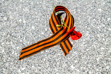 Victory Day. St. George ribbon on a stone plate. Red flowers on a stone slab. Symbol of Russian military glory and victory in the Great Patriotic War.
