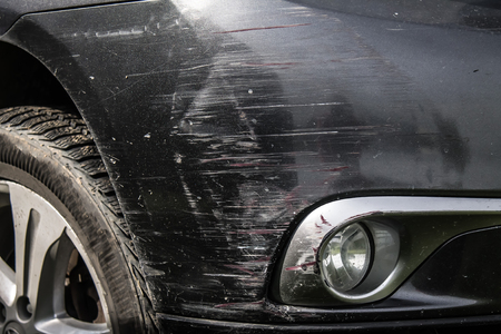 Black car bumper scratches close-up