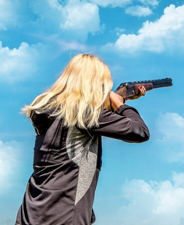Young girl with blond hair with a weapon for shooting at flying targets against the sky with clouds
