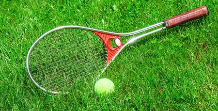 Tennis ball and racket on the green grass of the court close-up