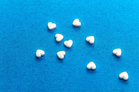 White dragee in the shape of a heart on a blue background. Beautiful background of hearts. The concept of love and romance. Stockfoto