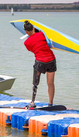 A girl with a prosthetic leg is engaged in rowing. The concept of people with disabilities go in for sports