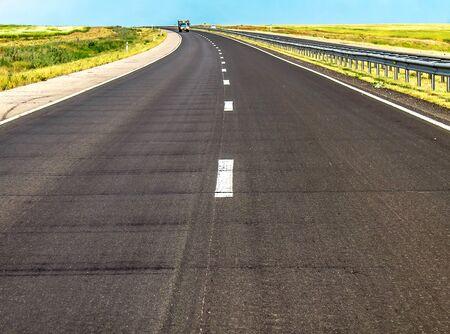 Asphalt Road leaving a blue sky landscape 写真素材 - 128773095