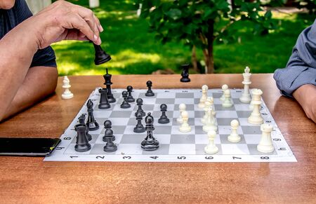 In the city park people play chess close-up. The concept of leisure of the elderly