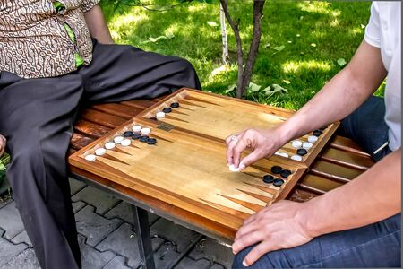 In the city park people play backgammon close up. The concept of leisure is the elderly. 스톡 콘텐츠