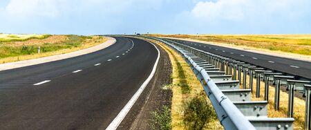 Asphalt Road leaving a blue sky landscape 写真素材 - 128773610