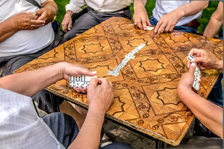 In the city park people play dominoes bones in close-up. The concept of leisure is the elderly.
