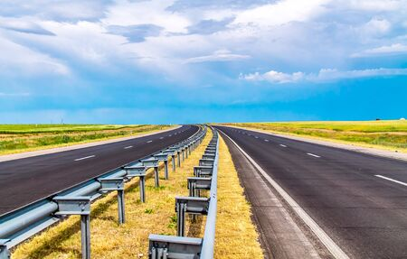 Asphalt Road leaving a blue sky landscape 写真素材
