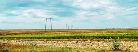 Metal supports high-voltage power lines on a wheat field. Landscape 写真素材 - 128773754