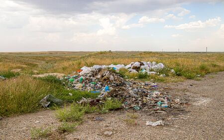Ecological pollution of nature. Waste of human activity on the side of the road in the Kazakh steppe.