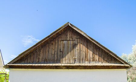 Old wooden roof gable on the sky background Stock Photo