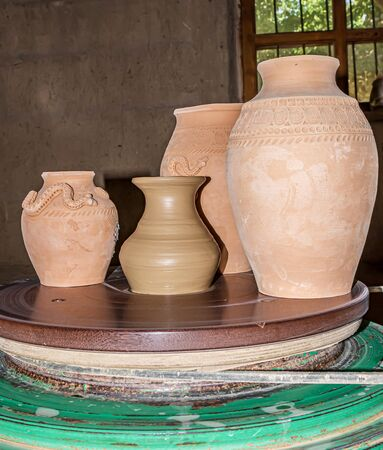 Clay jugs on a pottery wheel in a pottery workshop