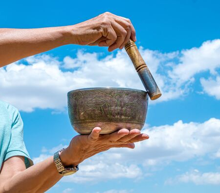A man plays the National musical instrument Tibetan singing bowl against the sky close-up
