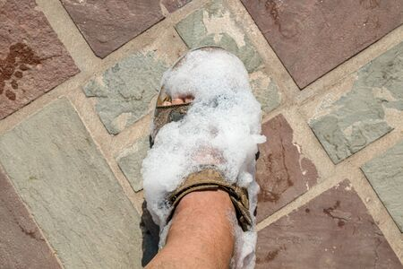 Foam on the feet of man in nature