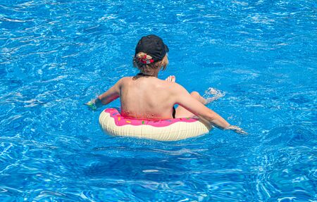 Girl swims in the pool. Resort relaxation