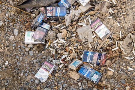 Various packs of cigarettes and cigarettes on earth are rubbish. Environmental disaster.
