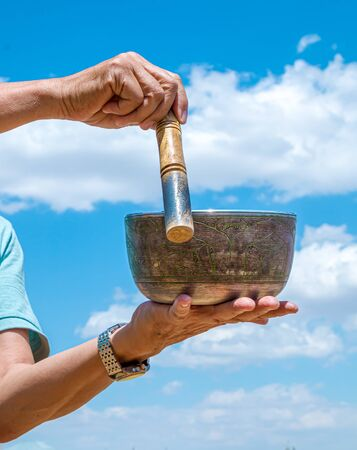 Ein Mann spielt die tibetische Klangschale des nationalen Musikinstruments gegen den Himmel aus nächster Nähe