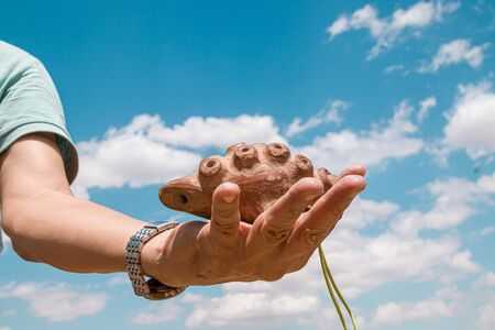 Ancient Asian musical instrument made of clay Otrar uldek in hand against the sky