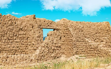 The destroyed walls of the building of clay against the sky. The walls of the ancient city of Otrar in Asia