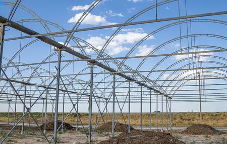 Metal frame in the construction of greenhouses against the sky