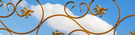 Painted gold paint forged metal products against the sky as a background for design