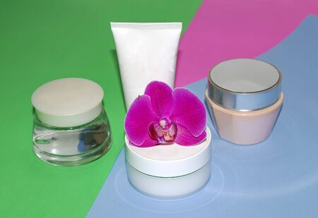 Face and body skin care. A set of white cosmetic tubes and cans on a pink background. Spa treatments at home.