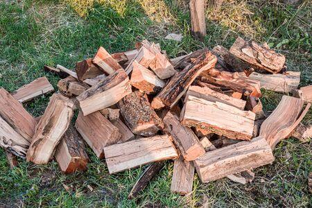 Chopped firewood on green grass close-up