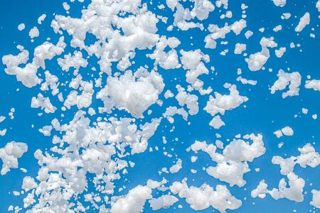 Soap foam on the background of blue sky as a background for design. Atmosphere of a holiday and summer outdoor recreation.