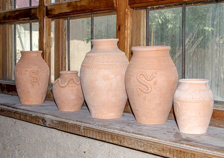 Clay jug on the window in the pottery workshop