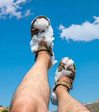 Foam on human feet against the sky