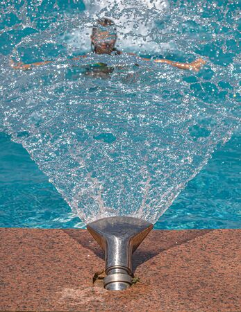 Fountain in the pool close-up. Children in the pool under water drops. Resort relaxation. Banco de Imagens