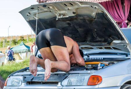 A man in shorts repairs cars in the field. Autotravel concept. Car breakdown. Car repair.