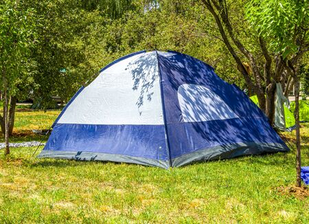 Tent under the trees. Wild outdoor recreation.