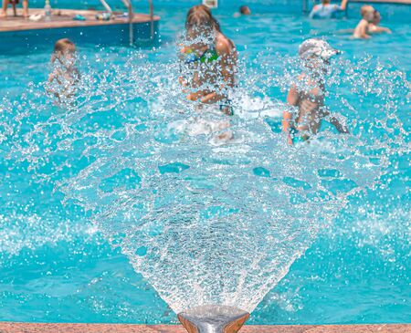 Fountain in the pool close-up. Children in the pool under water drops. Resort relaxation. 스톡 콘텐츠